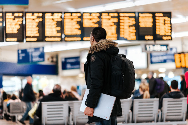 Man looking at departure board in an airport.
