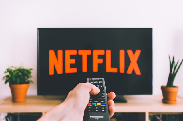 TV remote pointing at a screen showing Netflix