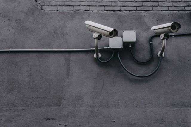Two mounted surveillance cameras on a wall